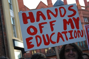 man holding protest sign Hands off my education
