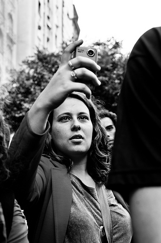 black and white photo of woman with camera in crowd