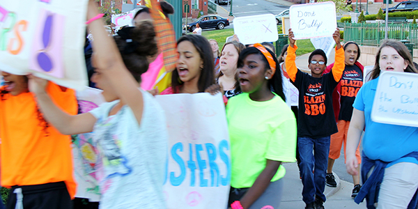 group of young upstanders marching protesting for anti bullying rally