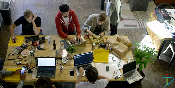 6 people sitting around table with computers at hackathon