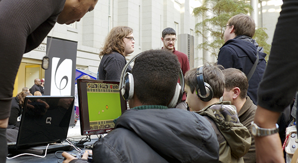 group of students playing computer games at museum