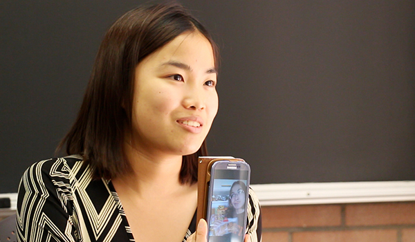girl in classroom showing selfie photo on her cell phone