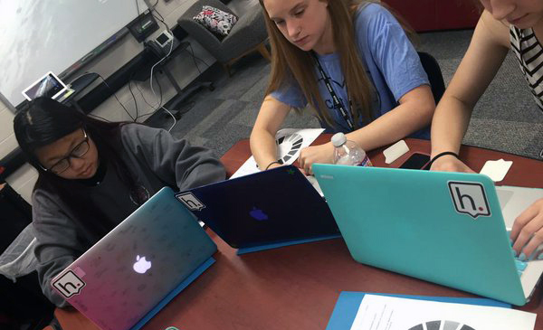 3 young female students sitting at table and looking at their laptop screens