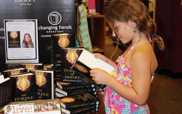 young girl reading book while standing in front of other books