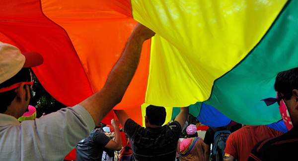 People standing under a large LGBTQ flag