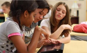 three girls composing letter on ipad