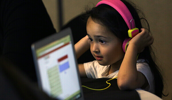 girl with headphones on and laptop