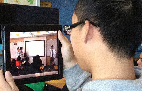 boy holding ipad watching classroom video