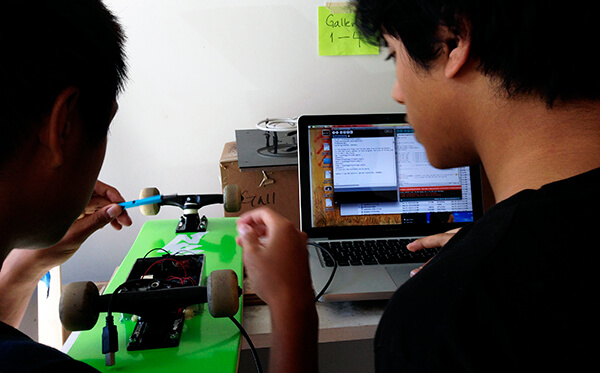 Teens working on Arduino micro controller to create technology enhanced skateboard
