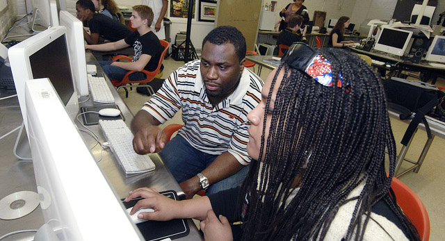 person helping student on the computer