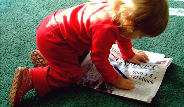 child drawing on newspaper