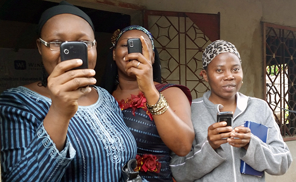 three women using cellphones to take pictures