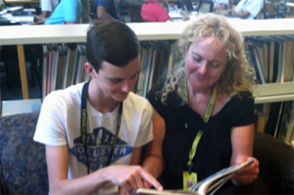 Student and teacher reading book together