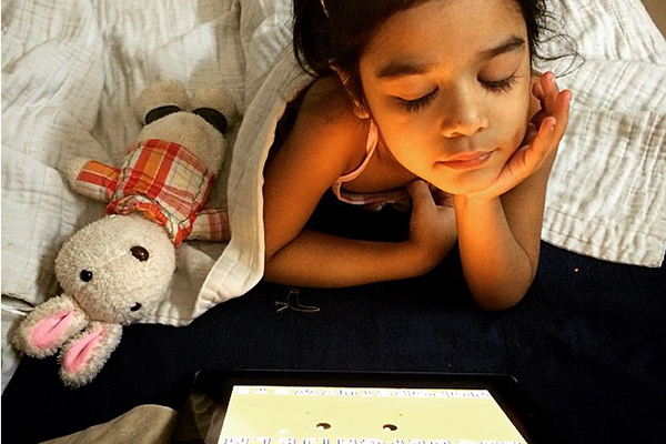 young girl in bed looking at screen