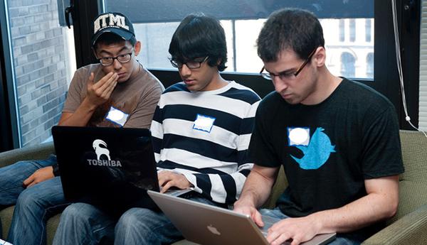 three students on laptops