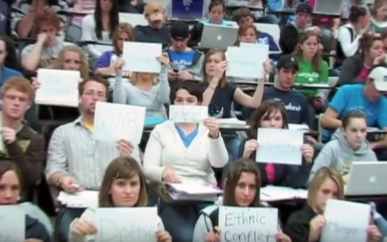 Students in Michael Wesch class holding papers with words written on them