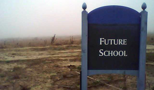 a sign that says future school before an empty lot