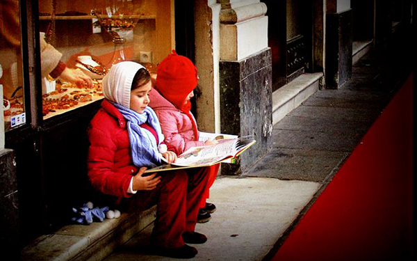 girls reading books on a bench