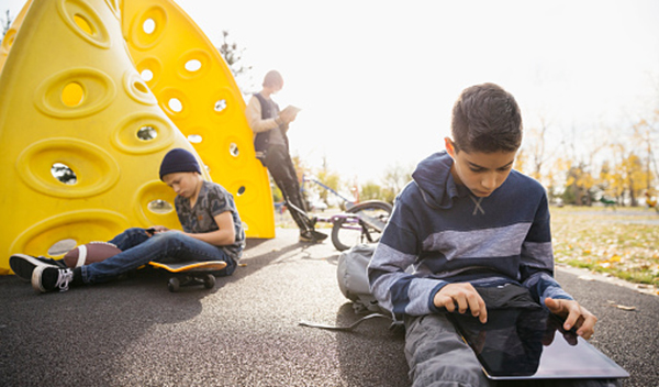 Tween boys using digital tablets and cell phone in sunny autumn park
