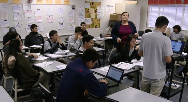 Teacher standing in middle of classroom surrounded by students