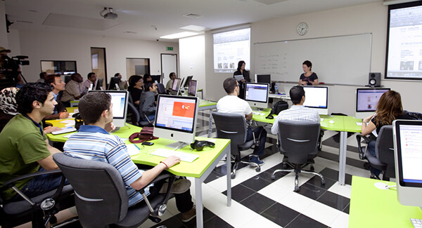 Young adults sitting in classroom with computers at every desk