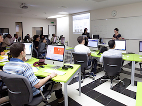 Young adult students sitting at desks with computers and facing toward front of class