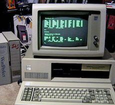 Personal computer from the 1980s sitting on a desk with green text on the screen