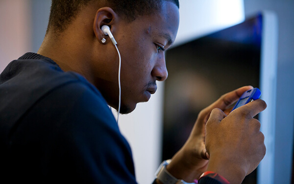 Young African American man looking at smartphone with earphones in his ears