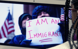 "Person holding a sign that says ""I am an immigrant"""
