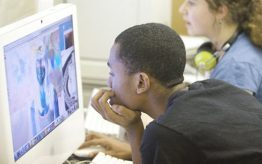 Young African American boy leaning over looking at computer screen