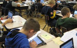 Kids looking at ipads in classroom