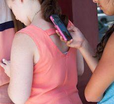 Teens looking at smartphone screen