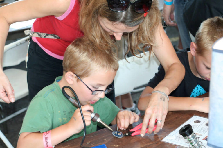 Woman standing over the shoulder of a child while he solders something