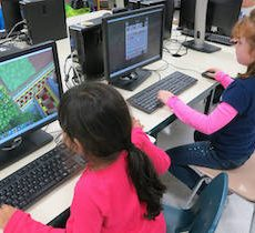 Young children playing games on computers