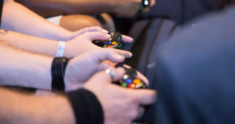 Close up of hands holding game controllers
