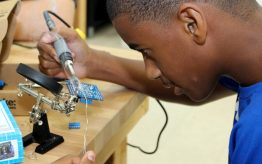 Young teen using soldering iron on electronics