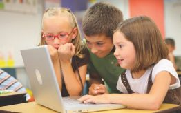 3 young kids playing on a laptop computer