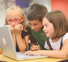 Three small children looking at laptop screen