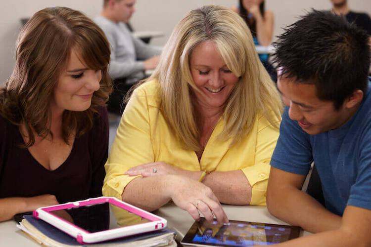 Educator and students looking at ipad
