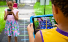 Kids playing math games outdoors on ipads