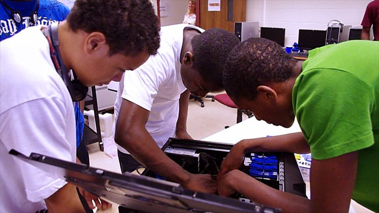 3 young boys taking apart and rebuilding a PC computer in classroom