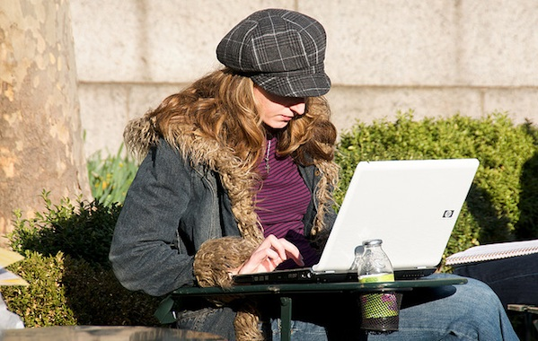 young girl sitting outside working on laptop