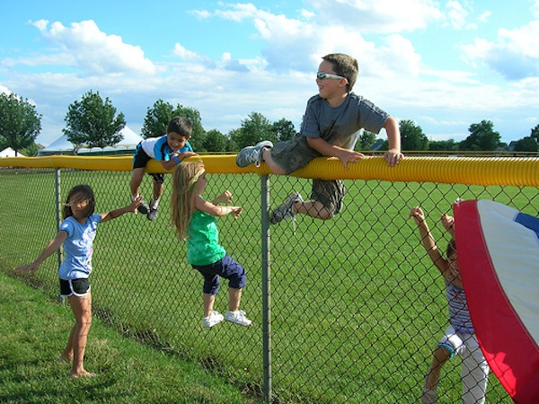 kids playing in field and climbing over fence