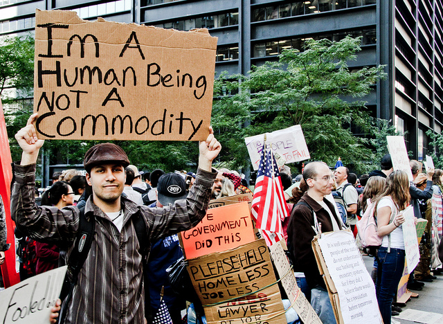 occupy wall street protest rally people marching holding up sign that says Im a human being not a commodity