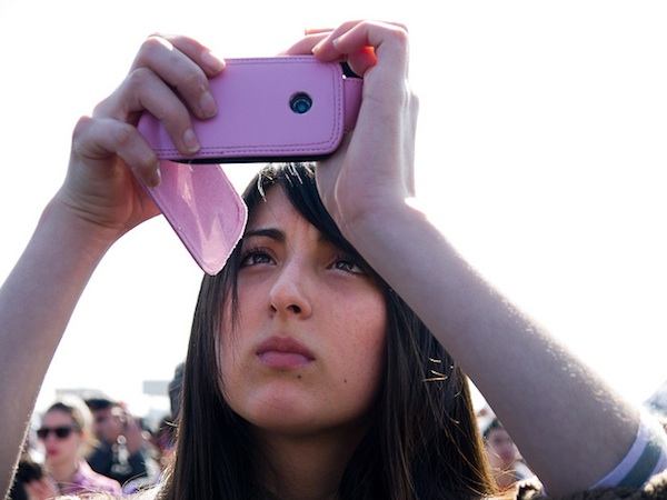 girl holding up camera phone in crowd taking a photo
