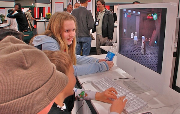 kids playing video games at school fair on computer
