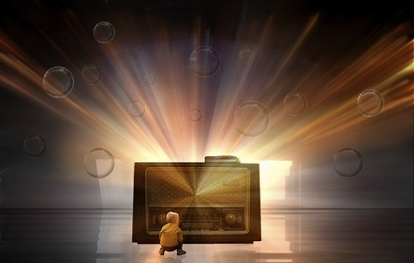 a child sitting in front of a radio with bright lights and bubbles representing imagination