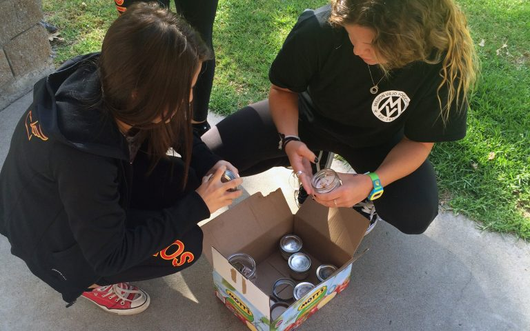 2 girls squatting over a box with jars inside