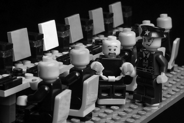 lego pieces characters sitting at lego computers one being arrested by police