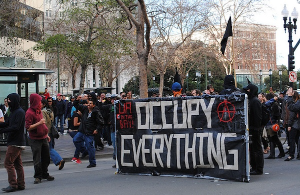 group rallying holding signs for occupy everything protest